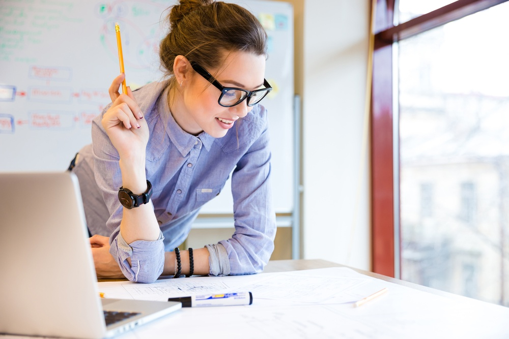 Happy young woman in glasses standing near the window in office and working with blueprint.jpeg