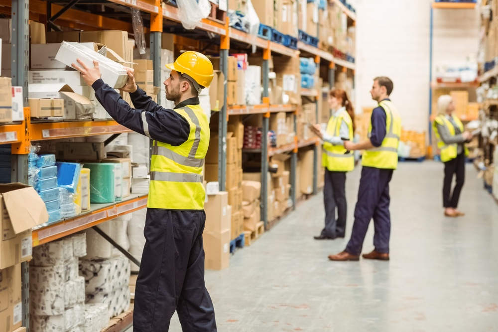 Warehouse worker taking package in the shelf in a large warehouse in a large warehouse